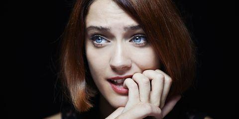 A woman feeling anxious biting nails
