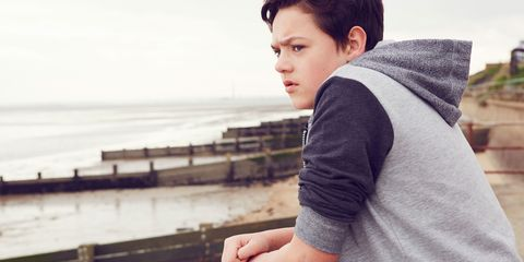 A boy looking out to the sea looking depressed