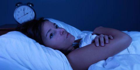 Woman awake at night. Clock shows 2am