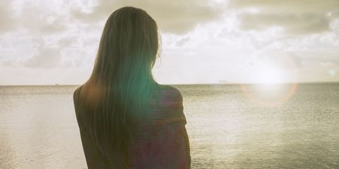 Back view of woman staring into the sea