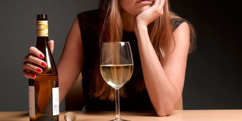 a woman drinking  a bottle of white wine
