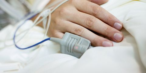 Hand in hospital bed attached to sensors and cables