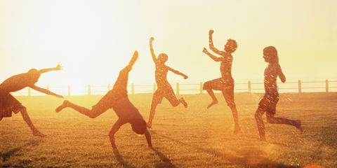 children dancing in a field in the sun