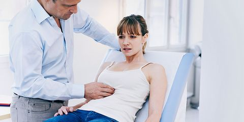 Doctor with hands on woman's stomach