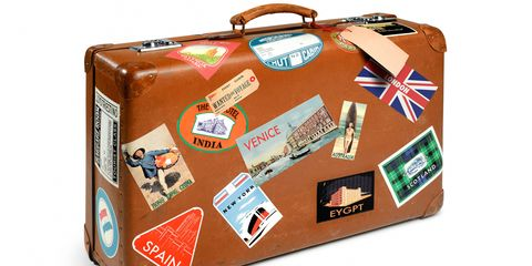A suitcase with stickers from around the world on it