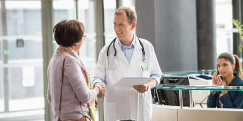 A mature woman shakes a doctor's hand