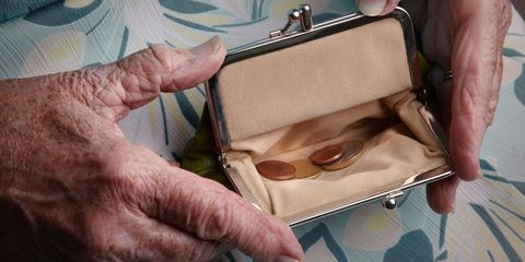 elderly woman holds open coin purse with money in it