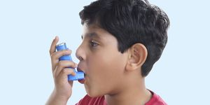 boy using blue preventer asthma inhaler