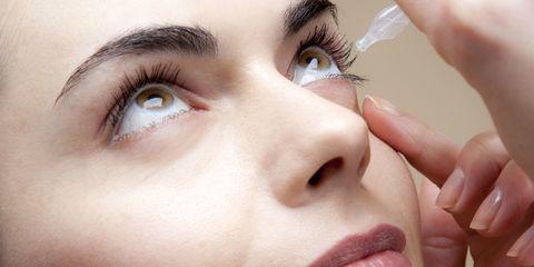 woman using eye drops vial