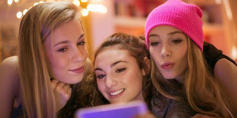 Teenage girls on phone taking  a selfie
