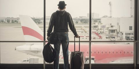 man looking out at aeroplane in terminal building