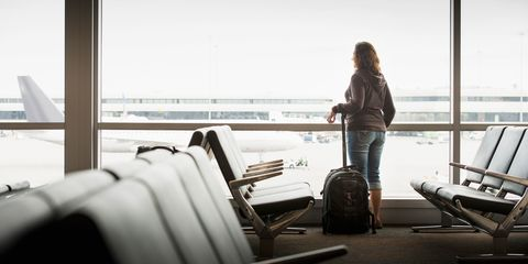 woman staring out of window at airport terminal