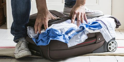 man with one foot on suitcase trying to stuff clothes into it