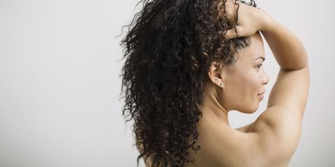 Woman with curly hair and bare arms smooth skin