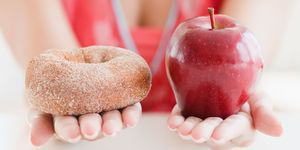 Close up of woman holding doughnut and apple