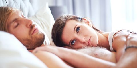 Woman lying in bed with insomnia can't sleep