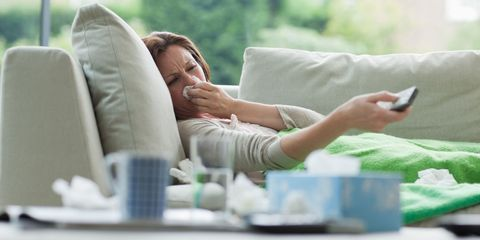 Woman blowing her nose ill on the sofa