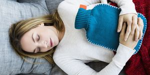 Woman lying on sofa with heating pad and stomach ache