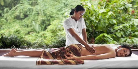 Woman having a massage in a jungle spa