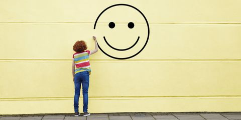Happy woman painting smiley face on wall