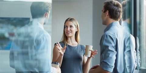 Confident woman speaking to male colleagues in office