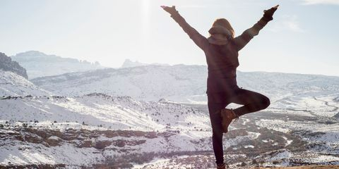 Woman doing yoga on a snowy mountain top