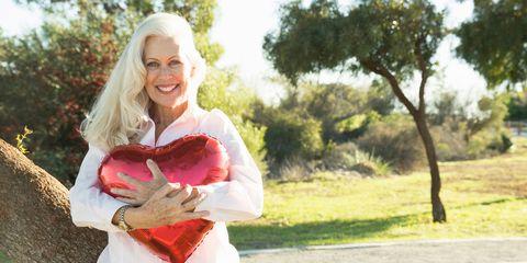 Older woman holding heart balloon