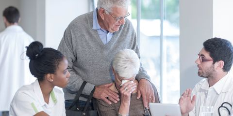 Older woman being told bad news by doctor being comforted by husband