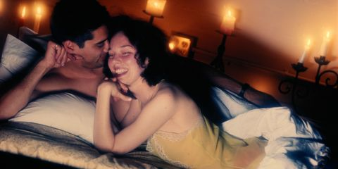Couple in bed surrounded by candles