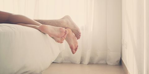 Couple lying in bed feet view