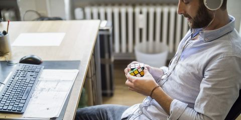 Young man in office at desk with Rubiks cube
