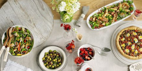 Selection of Mediterranean-style dishes, halloumi salad, seafood salad, olives and savoury brioche tart, summer berries, laid out on outdoor table