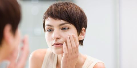 Woman with good skin cleanses her face in mirror