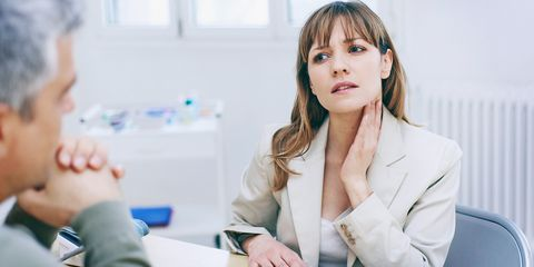 Woman with doctor holding throat sore