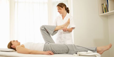 Physio stretching out patient