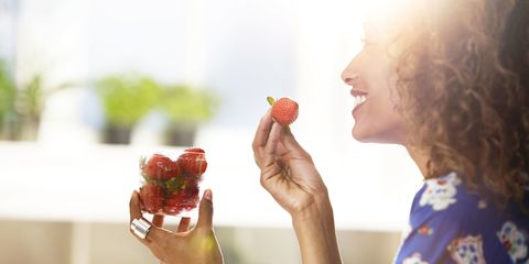 Healthy woman eating strawberries