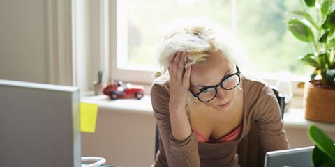 Woman working at desk stressed and tired
