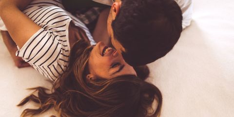 Couple laying in bed kissing and laughing