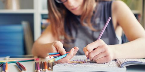 Woman colouring in an adult colouring book with pencils