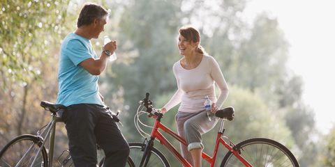 Healthy older couple drinking water on bicycles