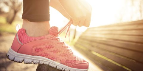 Woman ties running shoes on bench