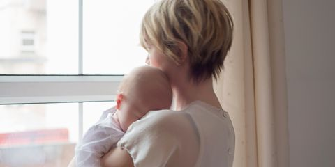 Mother holding baby looking out the window sad