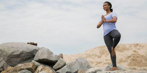 Woman doing a yoga pose on rocks near the seaside