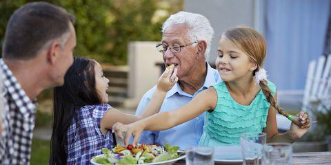 Grandpa and grandchildren having dinner