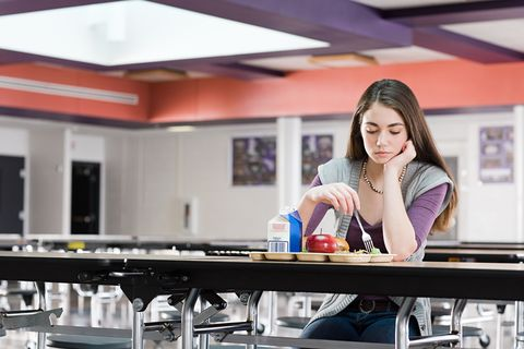 Woman eating lunch alone sad