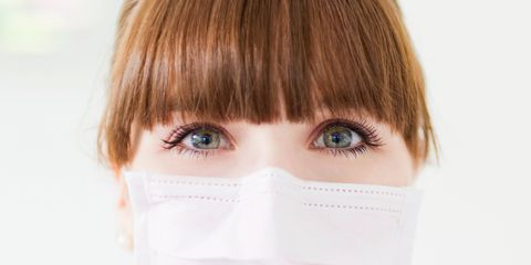 Woman with green eyes wearing a protective mask over her mouth