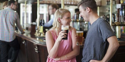 Couple drinking pints of beer in a pub