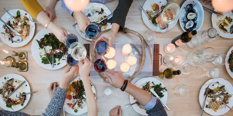 Group of friends eating dinner and drinking wine