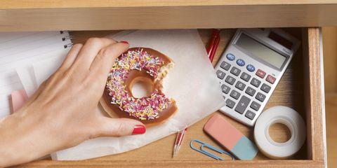 Woman reaching for hidden donut in desk