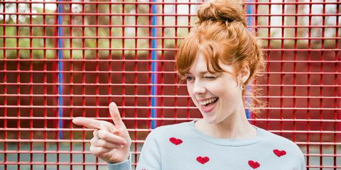 Redhead woman smiling winking and pointing infront of railings